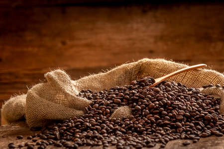 Close-up view of sack of spilled fresh coffee beans with wooden spoon on brown background