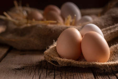 Fresh chicken eggs in farm lying on linen cloth on wooden table Stockfoto