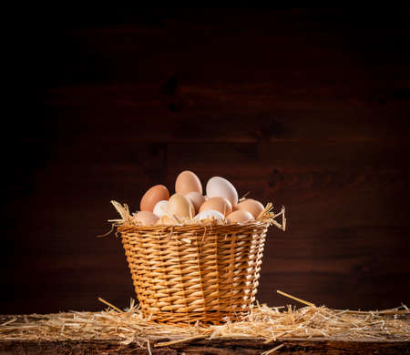 Wicker basket with fresh raw eggs on dark background Banque d'images
