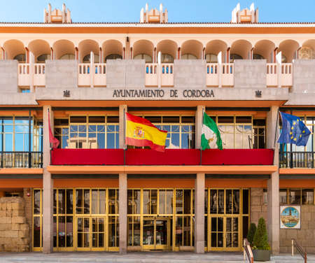 Cordoba, Spain - Oct 29, 2018: Exterior facade of Cordoba City hall with waving flags in Cordoba, Spain on October 29, 2018