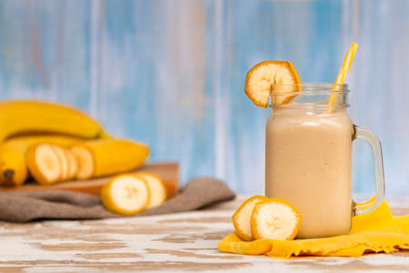 Tasty fresh drink in glass mug with plastic tube and slice of banana on napkin near fruits and bananas on chopping board on wood table