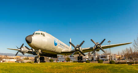 Cordoba, Spain - February 14, 2019: Aged airplane DC7 exhibited on green lawn of country under clear blue sky in bright sunshine in Cordoba, Spain on February 14, 2019