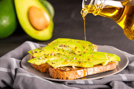 Fresh oil pouring over yummy sandwiches with avocado slices and spices