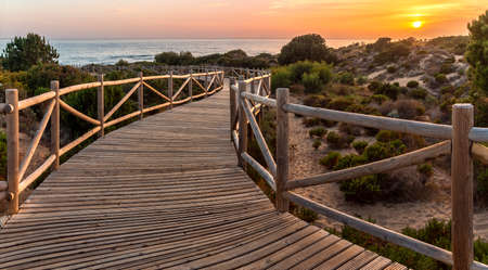 Weathered lumber path leading to calm sea during beautiful sunset in countryside in Cabopino, Artola dunes. Marbella, Spain