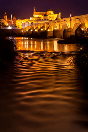Ancient stone Roman bridge illuminated in night time with glowing Moorish Mosque Cathedral (Mezquita) on background in Cordoba, Spain