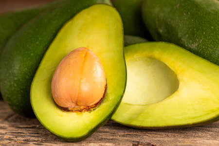 Closeup halves of fresh ripe avocado with big seed placed on plaster surface