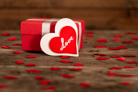Valentine's day greeting card for love with red and white heart shape and gift box on wooden