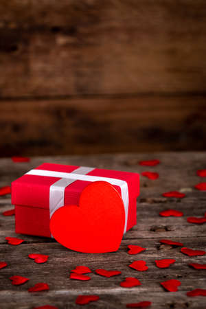 Valentine's day greeting card for love with red heart shape and gift box on wooden
