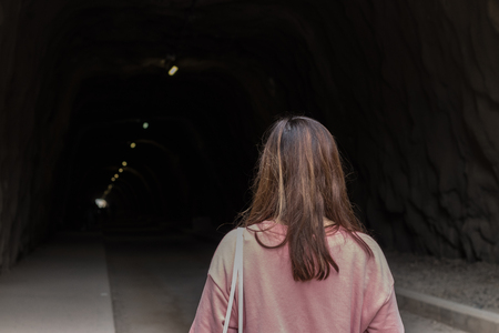 woman about to enter a dark and mysterious tunnel