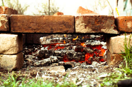 calorific: selfmade bricks brazier  with glowing coals outdoors