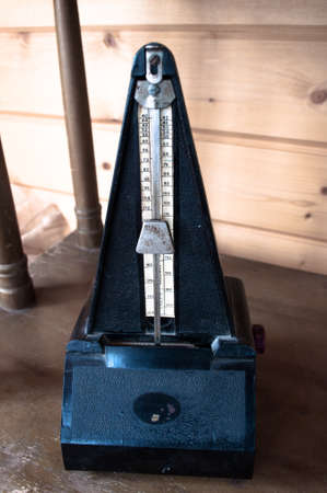 metronome: Retro black metronome on vintage wooden background