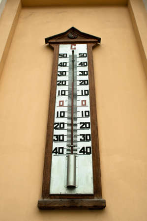 weather gauge: A large wall-mounted mercury temperature gauge outdoors