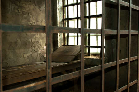 Wooden bed in a medieval prison cell near the window Stock Photo