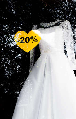 yellow dress: White wedding dress  with sale sign of a twenty percent discount in the window