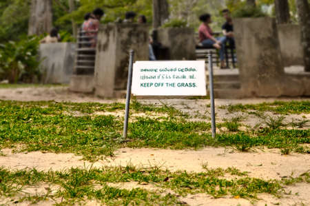 Keep off the grass sign in a tropical park with poor lawn in Colombo Sri Lanka