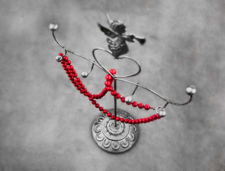 Red necklace on a metal stand with angel interior accessory in gray tones