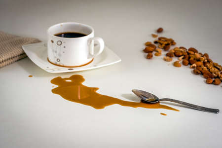 coffee mugs: Spilled coffee stain on the table during the breakfast.