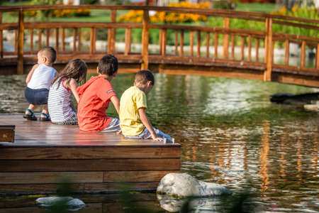 children pond: Istanbul, Turkey - September 6, 2015: Four children are sitting in the Goztepe park next to the pond in Istanbul, Turkey. Editorial