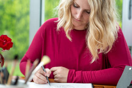 femme dessin: Blond artiste f�minine dessin au crayon sur la table