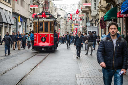 street shot: Istanbul, Turkey - November 06, 2015: People walking on Istiklal street while nostalgic red tram passing by. Istiklal avenue is the most famous street in Istanbul. Editorial