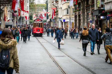 old buildings: Istanbul, Turkey - November 06, 2015: People walking on Istiklal street while nostalgic red tram passing by. Istiklal avenue is the most famous street in Istanbul. Editorial