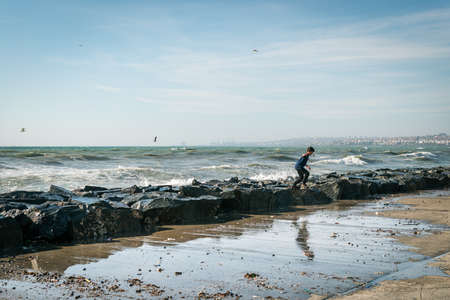 the marmara: Istanbul, Turkey - November 22, 2015: Boy is playing next to the Sea of Marmara during the strong wind in Istanbul. Wavy seascape. Editorial