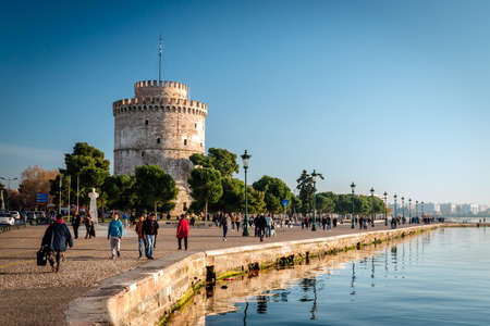 guarded: Thessaloniki, Greece - December 24, 2015: People walking on the coast in Thessaloniki next to the white tower which once guarded the eastern end of the citys sea walls Editorial