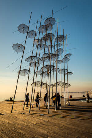 Thessaloniki, Greece - December 24, 2015: People are spending their leisure time near Umbrellas sculpture on Thessalonikis sea front.