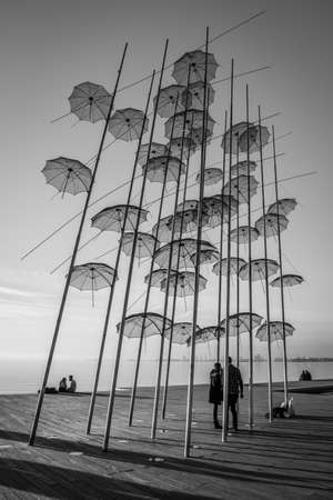holdup: Thessaloniki, Greece - December 24, 2015: People are spending their leisure time near Umbrellas sculpture on Thessalonikis sea front.