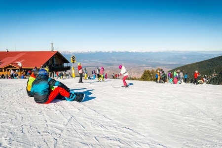 labelling: Bansko, Bulgaria - December 29, 2015: Skiers and snowboarders resting in ski resorts station up in the mountains.