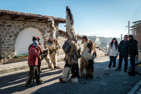 coming together: Dobarsko, Bulgaria - January 01, 2016: People are coming together for games and dances to celebrate the custom festival of Mummers Kukeri at January in Bulgaria