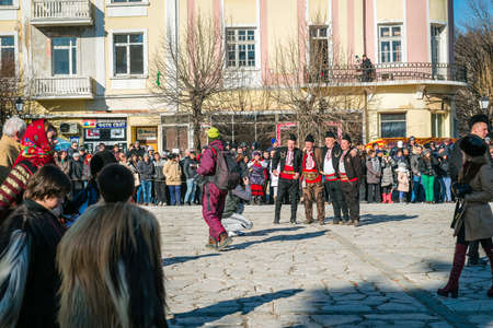 coming together: Razlog, Bulgaria - January 01, 2016: People are coming together in Razlog square to celebrate the custom festival of Mummers Kukeri at January in Bulgaria