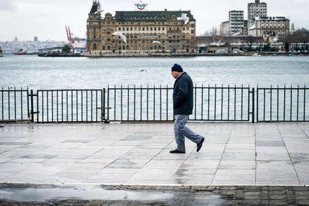 haydarpasa: Istanbul, Turkey - January 18, 2016: Man is walking on the coast in Kadikoy, on the background of Haydarpasa station. Editorial