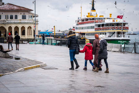 the turks: Istanbul, Turkey - January 18, 2016: People are walking near the ferry port in Kadikoy, on the background of ferry pier.