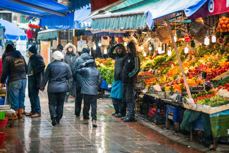 kadikoy: Istanbul, Turkey - January 18, 2016: People are passing by fruit sellers on kadikoy market in winter