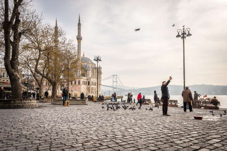 istanbul beach: Istanbul, Turkey - January 31, 2016: People spending weekend and feeding pigeons in Ortakoy near beautiful mosque and Bosphorus in Istanbul.