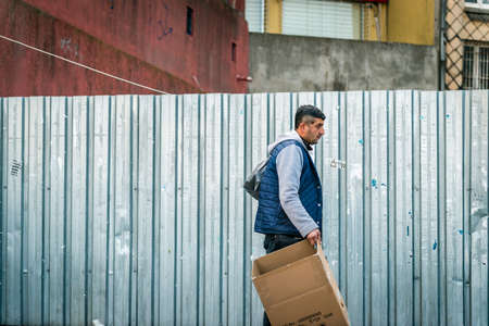 turkish man: Istanbul, Turkey - January 31, 2016: Turkish man is walking on the street with box in his hands in Istanbul, Turkey