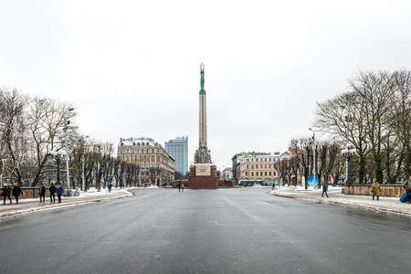socle: Riga, Latvia - February 20, 2016: People are walking near the Freedom Monument in Riga, Latvia