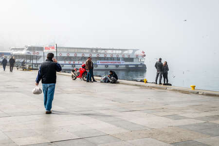 kadikoy: Istanbul, Turkey - February 29, 2016: People are spending time near the port in Kadikoy in a very foggy day. Ferries doesnt serve because of weather conditions.
