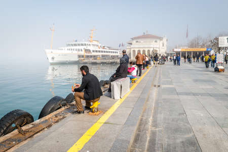 seabirds: Istanbul, Turkey - February 29, 2016: People are feeding seabirds in the port of Kadikoy in a foggy day. Ferries doesnt serve due the weather conditions