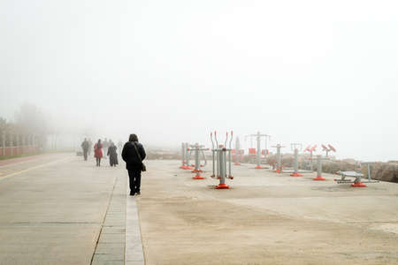 kadikoy: Istanbul, Turkey - February 29, 2016: People are passing by the outdoor fitness machines on the coast of Kadikoy in a very foggy day