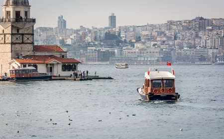 transfering: Istanbul, Turkey - January 21, 2015: Boat is transfering customers of the restaurant to the Maidens Tower in Istanbul, Turkey
