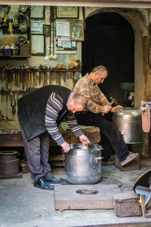 Istanbul, Turkey - March 10, 2015: Turkish men restores metal pots in Istanbul, Turkey Editorial