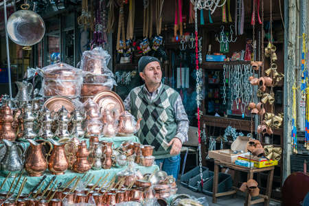 turkish man: Istanbul, Turkey - March 10, 2015: Turkish man is smoking and selling copper dishes in Istanbul, Turkey