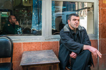 turkish man: Istanbul, Turkey - March 10, 2015: Turkish man sitting and smoking on the street next to the cafe in Istanbul, Turkey Editorial