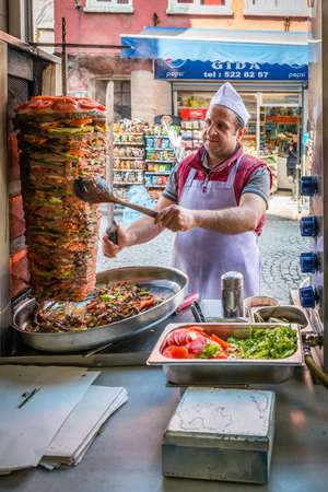 culinary tourism: Istanbul, Turkey - March 10, 2015: Man is cooking rotary or doner on the street in Istanbul, Turkey