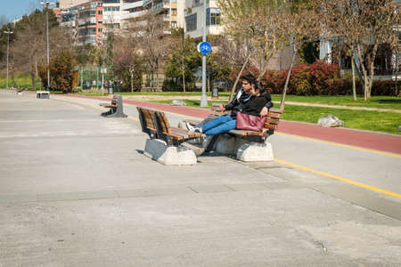 kadikoy: Istanbul, Turkey - March 29, 2016: Young loving couple is sitting in Kadikoy on the bench in a sunny day in Istanbul, Turkey Editorial