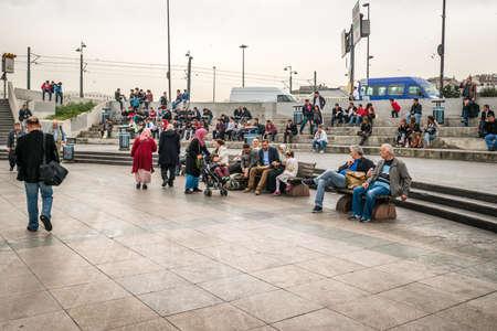 eminonu: Istanbul, Turkey - April 08, 2016: People are sitting and resting in Eminonu near of the Galata bridge in Istanbul, Turkey