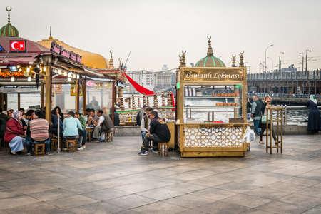 istanbul beach: Istanbul, Turkey - April 08, 2016: People are selling and eating fast food on the coast of Eminonu near the Galata bridge in Istanbul, Turkey Editorial