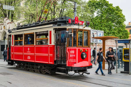 tramway: Istanbul, Turkey - April 08, 2016: People are walking down the Istiklal street near the  red tramway in Istanbul, Turkey Editorial